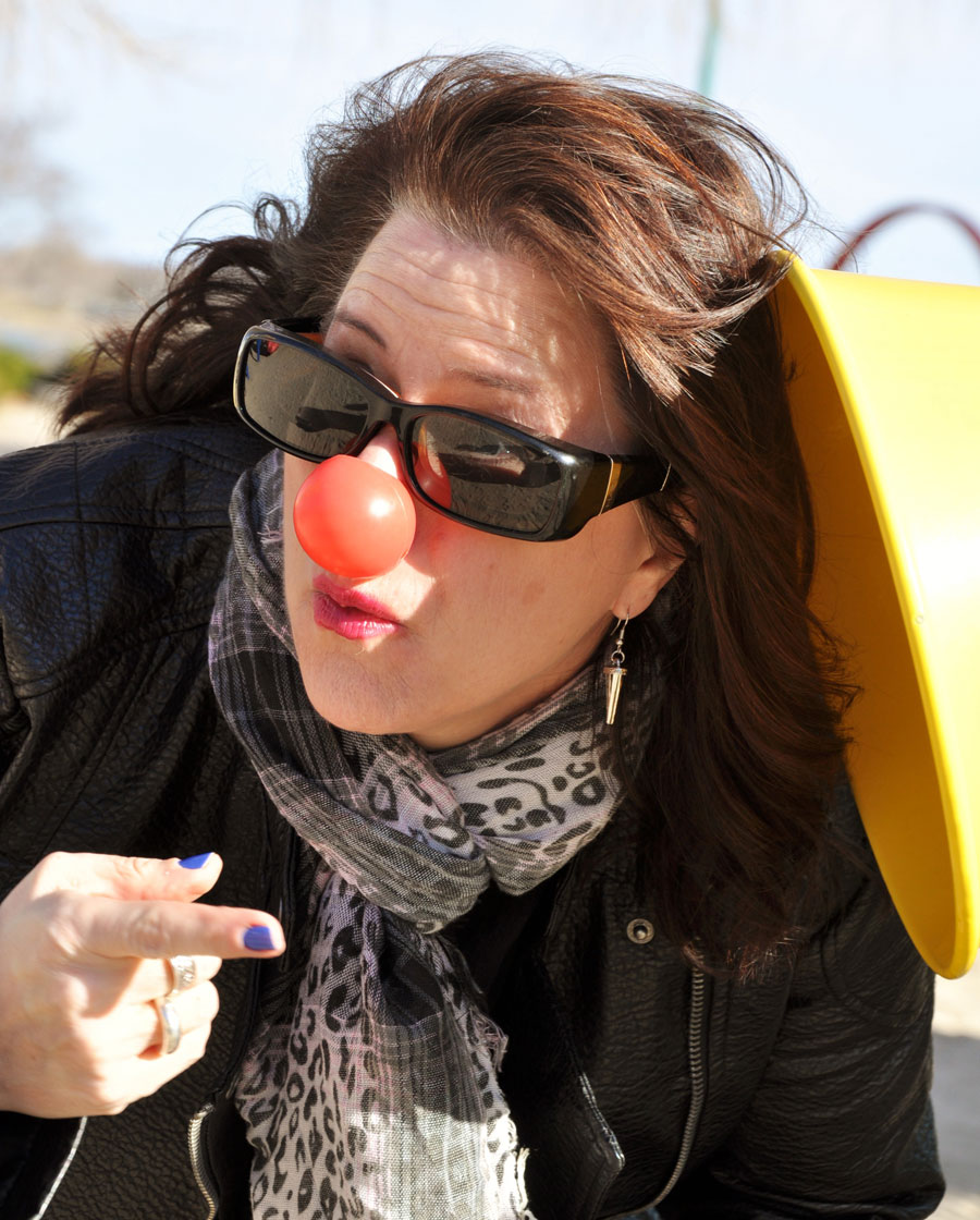 woman with a clown nose on at a park