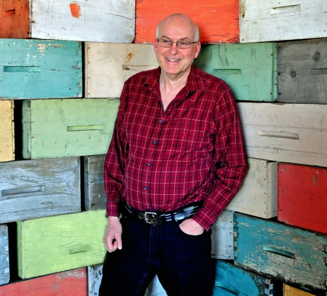 Man in red plaid shirt and dark jeans standing in front of wood boxes of all colours