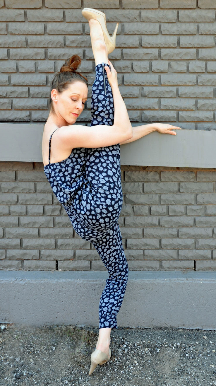 Female dancer with leg in the air, grey brick background, posing in dance move in alley