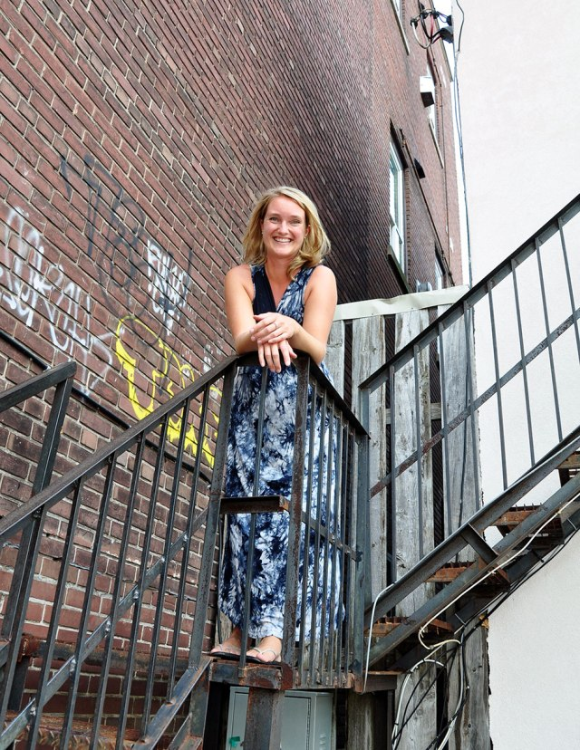 Young woman in dress standing on stairs outside appartment