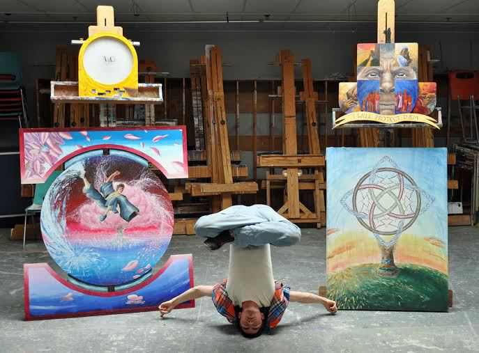 young man in yoga pose, art behind him