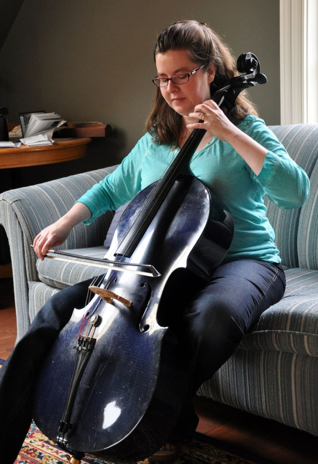 Women sitting on a couch playing a blue cello