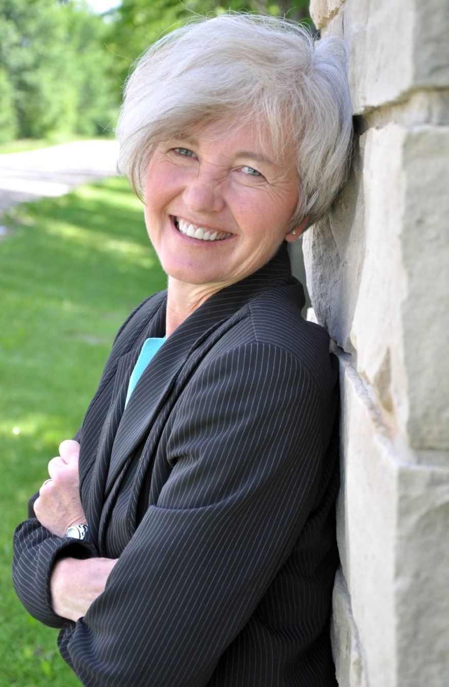 Woman with short hair and suit on smiling, leaning against brick wall