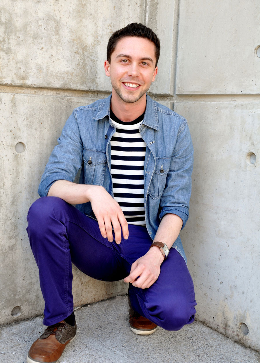 Young man with striped shirt, jean jacket and purple/bluey pants crouched in an ally way, all smiles