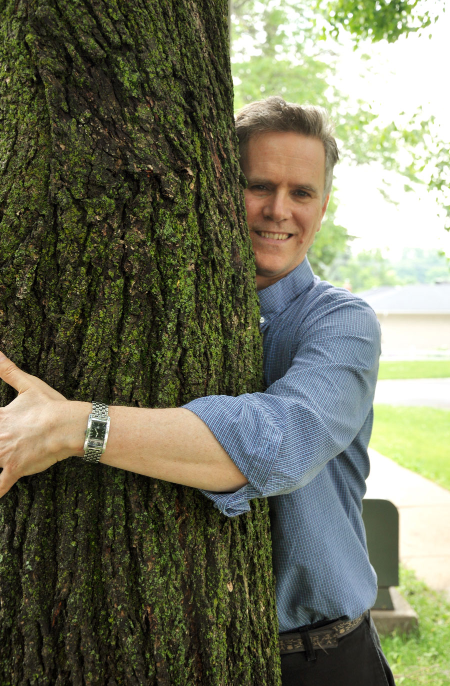 Man hugging a tree, wearing blue button up long-sleeved shirt