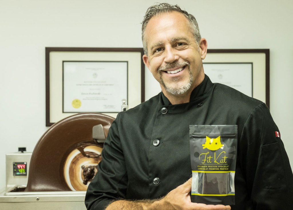 Man in black shirt holding up a bag of chocolate he created, all smiles