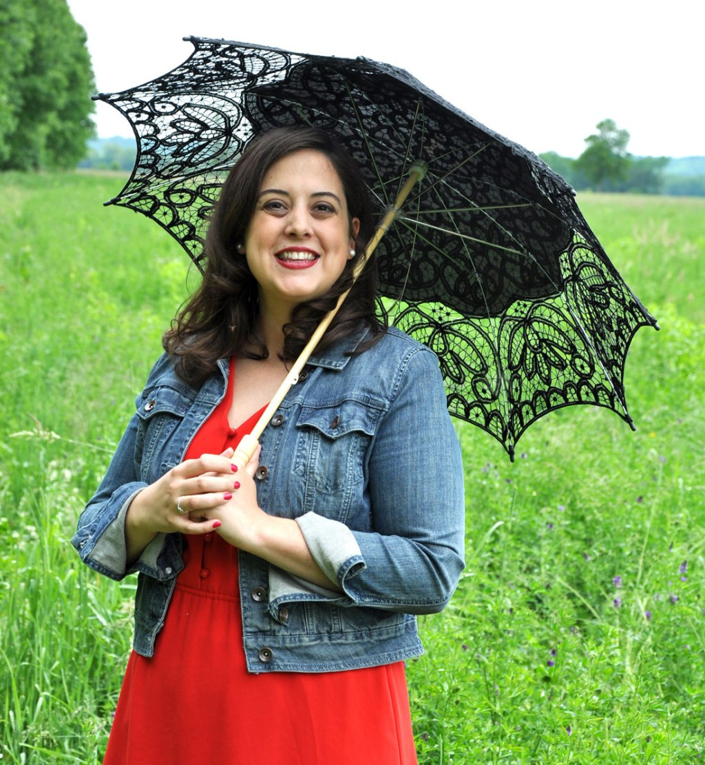 Woman in green field wearing red dress and jean jacket with black lacy umbrella, smiling