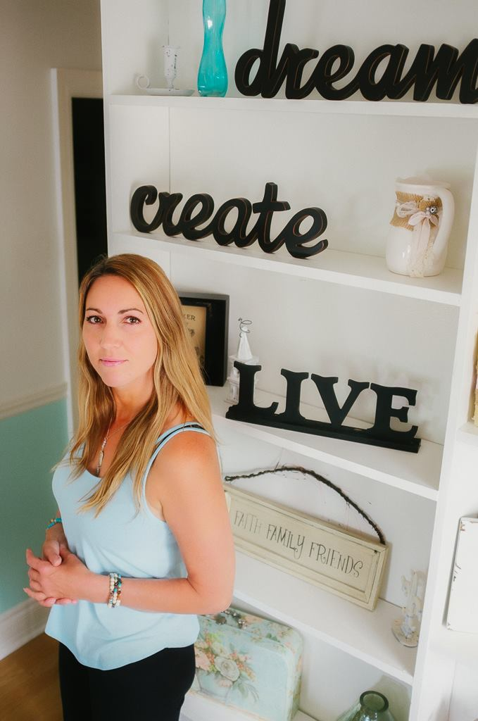 Young woman in tank top standing in front of dream, create, live sign in her home, long blonde hair, serious smile