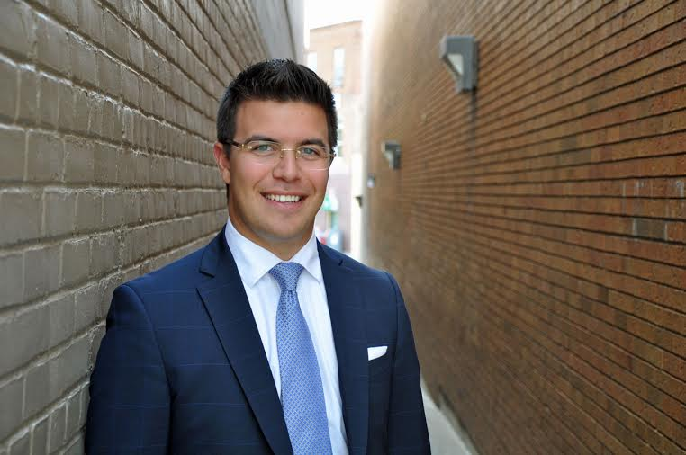 male in a suit in alley way, wearing glasses and blue tie