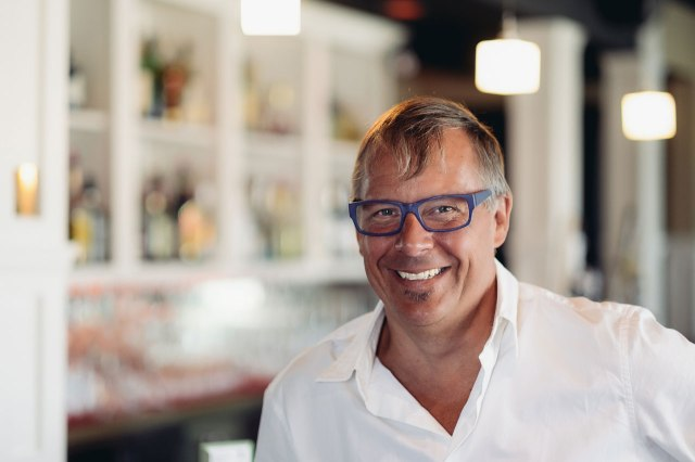 man in glasses and white dress shirt standing in his restaurant