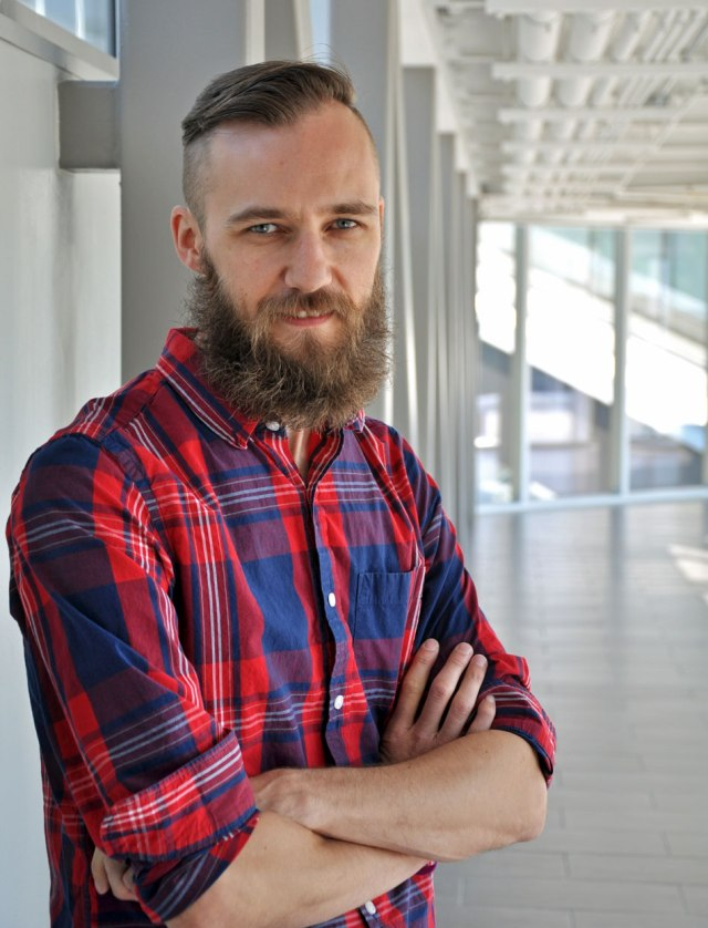 bearded man in plaid shirt, arms crossed in building