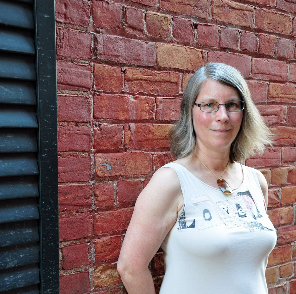 woman in white dress standing against red brick wall, wearing glasses, shoulder length hair