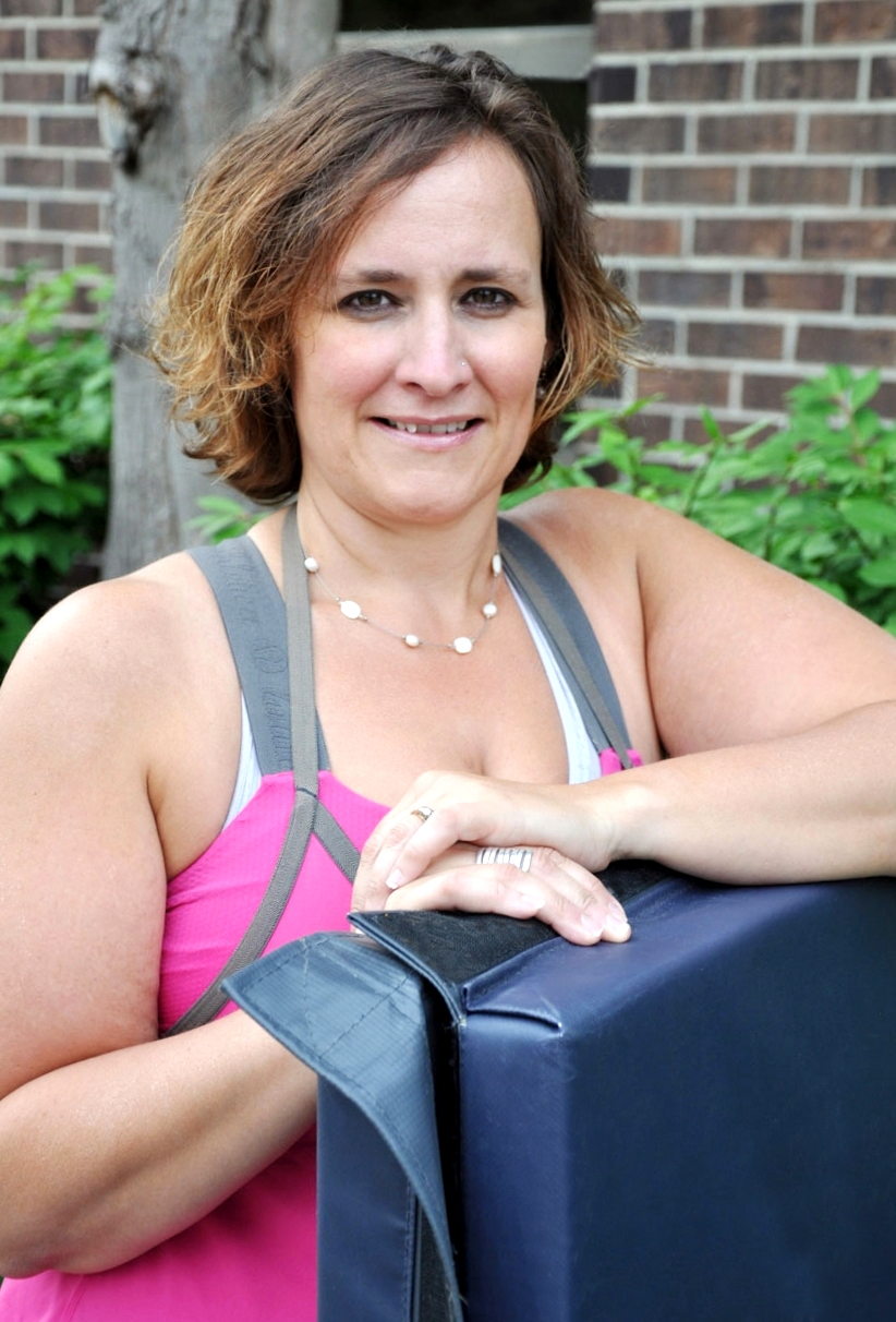 woman in workout gear leaning on a mat outdoors