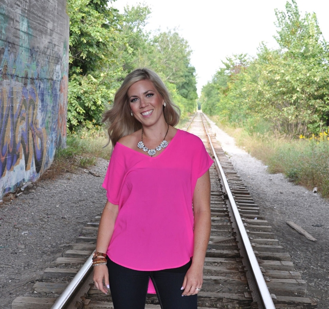 blonde girl with pink top standing in middle of railroad tracks, all smiles