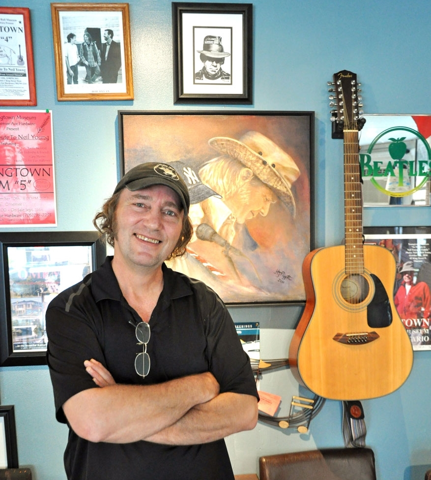 Man in black golf shirt, hat, standing with arms crossed, behind him a guitar and collage of photos