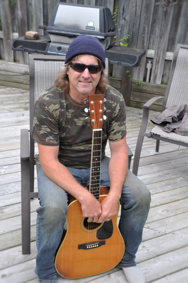 man in hat, sunglasses, army t-shirt and jeans sitting on patio with guitar