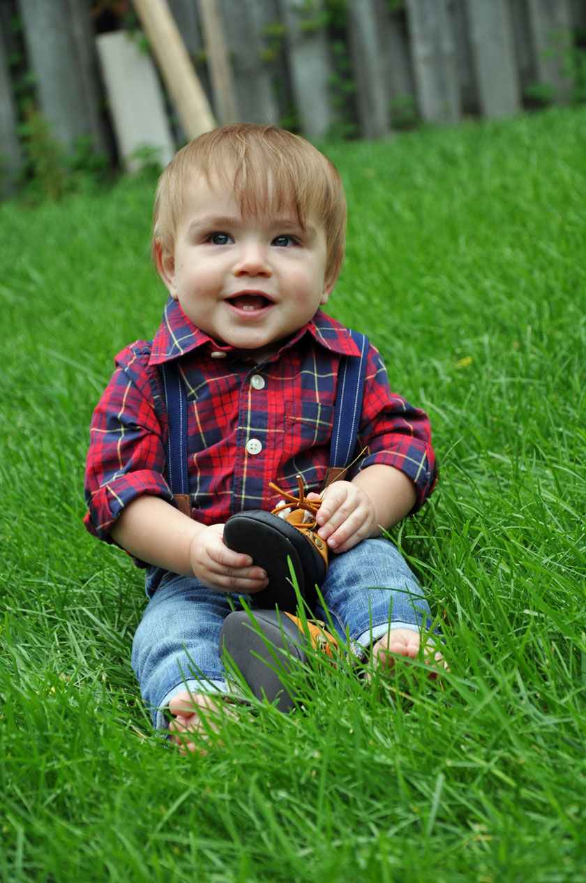 little boy sitting in the grass wearing jeans and a plaid shirt, holding toddler shoes