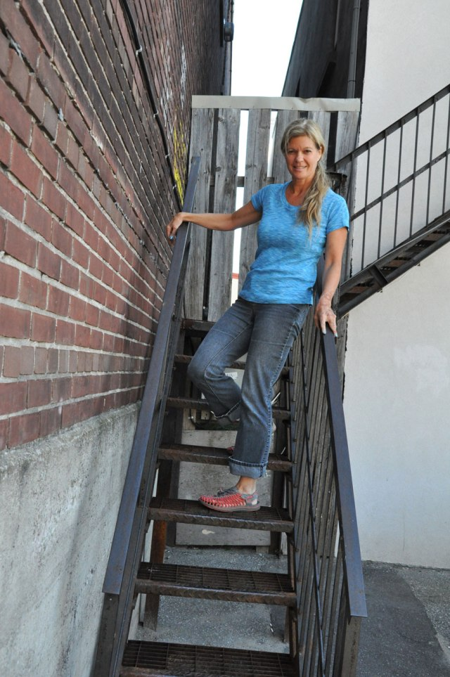 Woman in jeans and light blue tee standing on blackstairs in back alley downtown