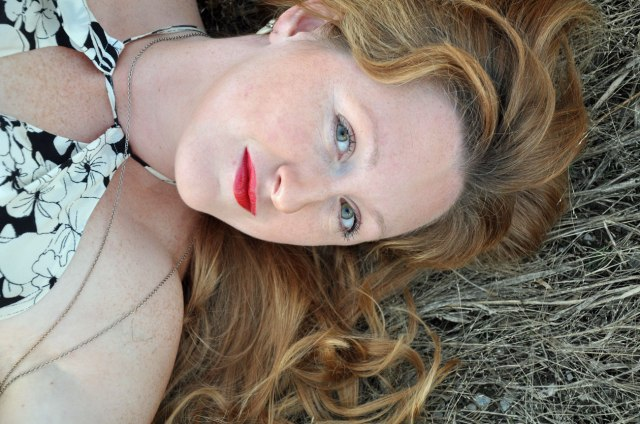 young woman lying in a field, red lipstick, shoulder length hair