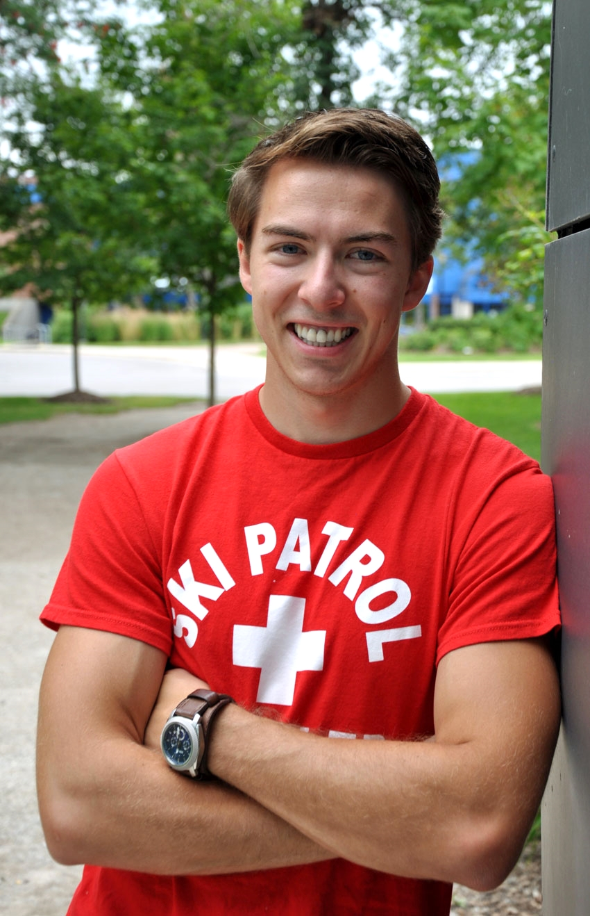 young man in red and white ski patrol t-shirt leaning against a brick wall