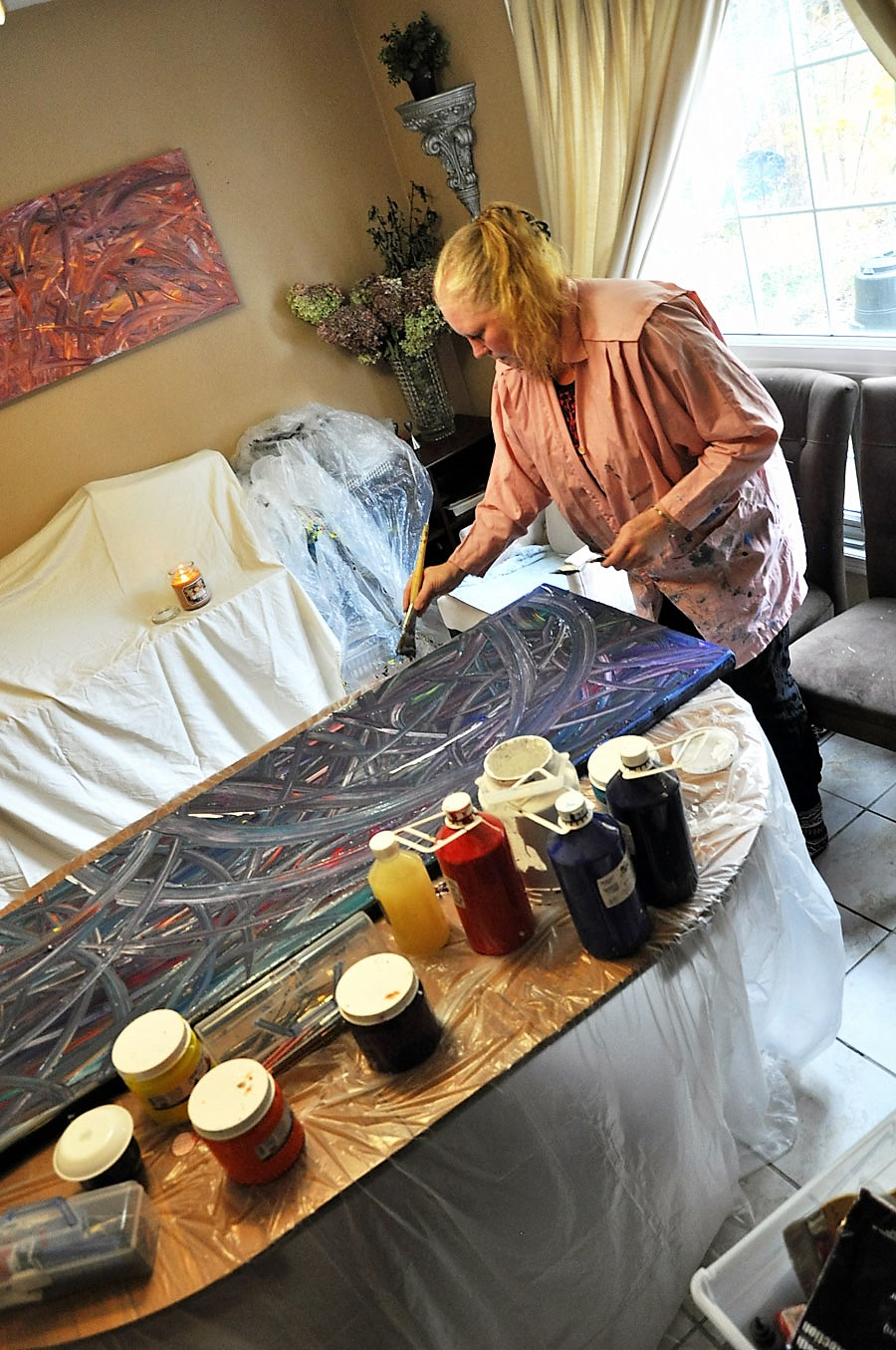Woman painting on a large canvas in her studio