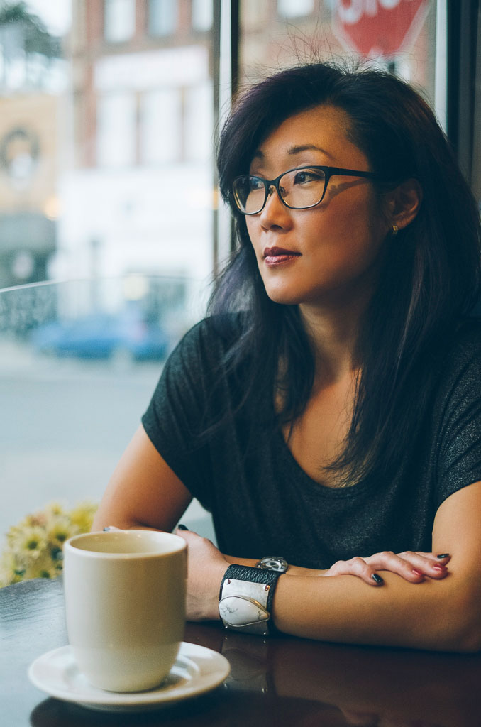 young asian woman in a coffee shop looking out the window