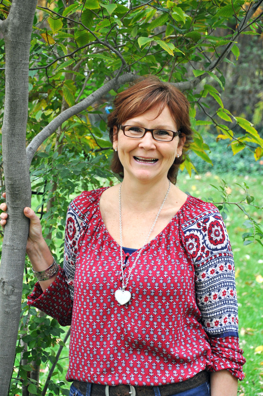 woman in colourful shirt, short dark hair and glasses, holding tree trunk