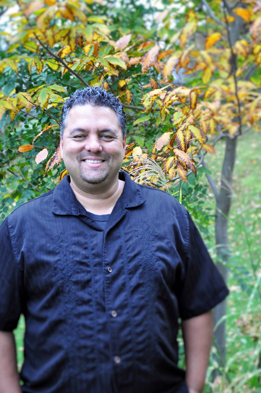 man in black short sleeved shirt standing in front of fall backdrop