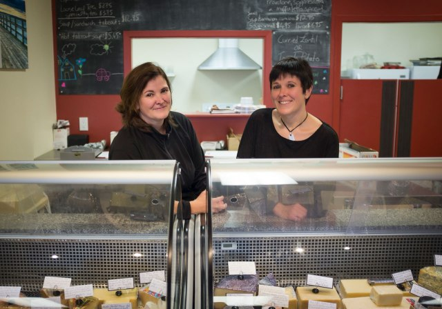 female twins in a cheese shop, behind the counter