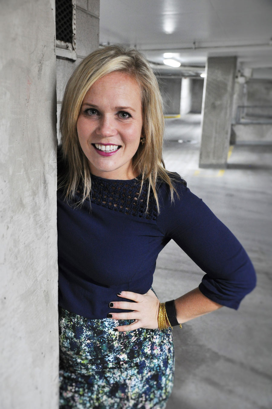young blonde woman in parking garage, peeking around the corner, wearing a long-sleeved blue top and print skirt