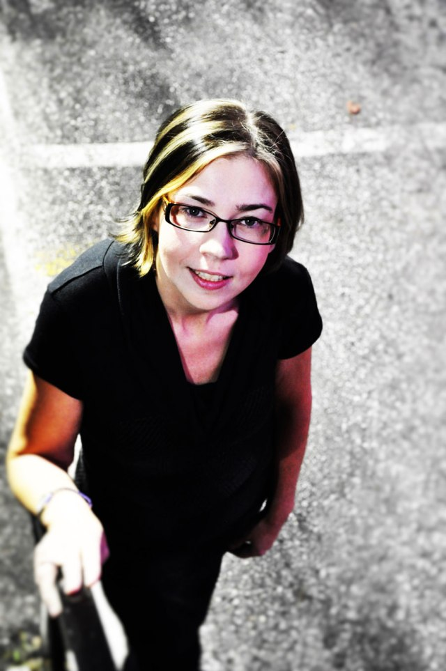 woman with short blonde hair, glasses, black dress, standing at bottom of stairs in parking lot, looking at camera