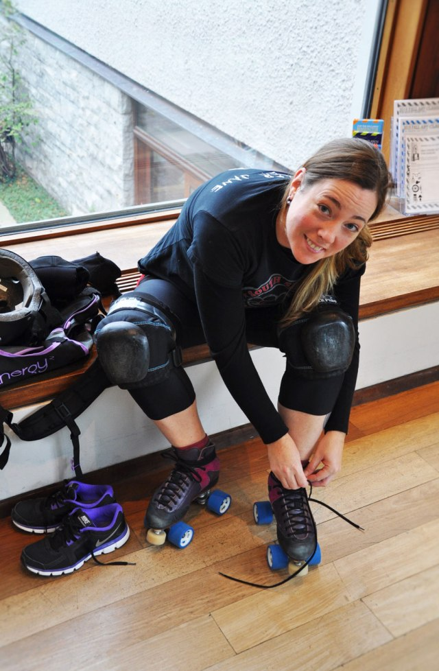 woman sitting down putting on her roller derby gear