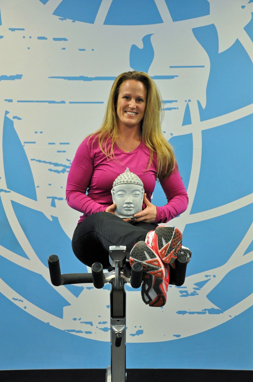 woman in pink shirt sitting on a bike with budda in her hand