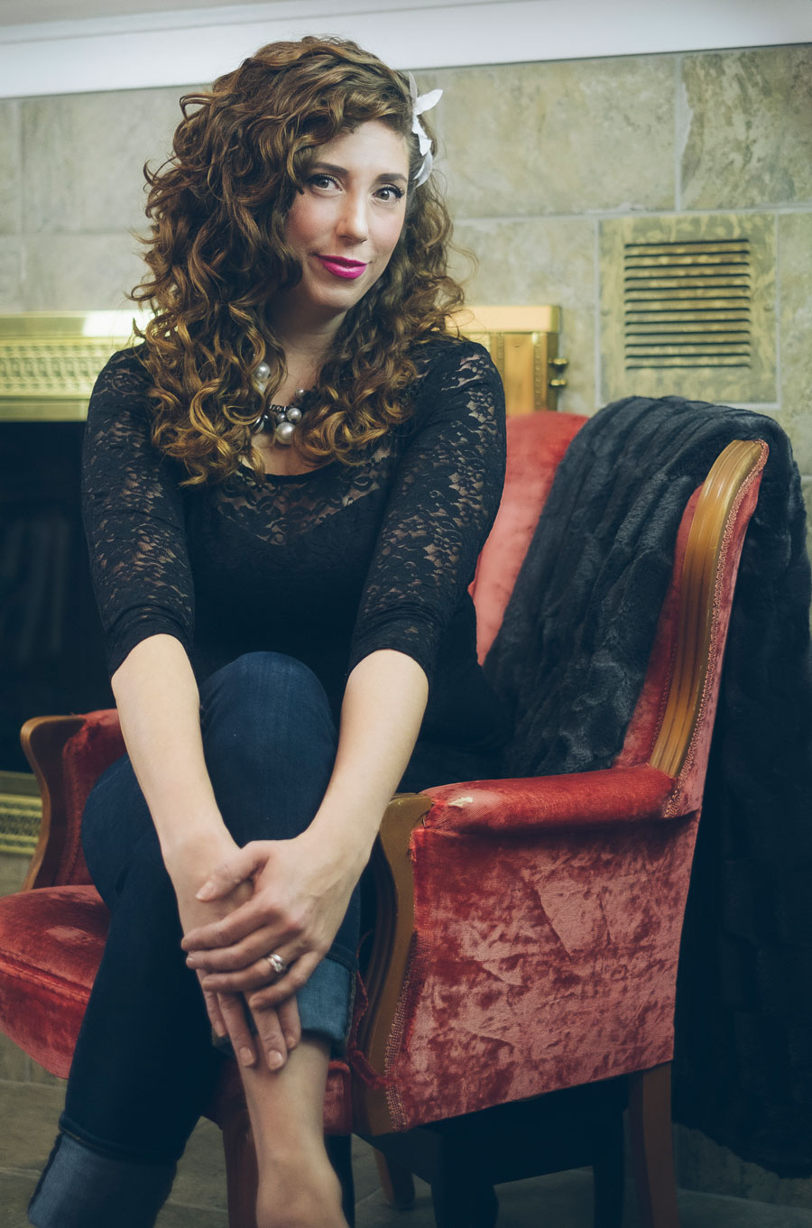 woman with long curly hair sits on red chair in parlour