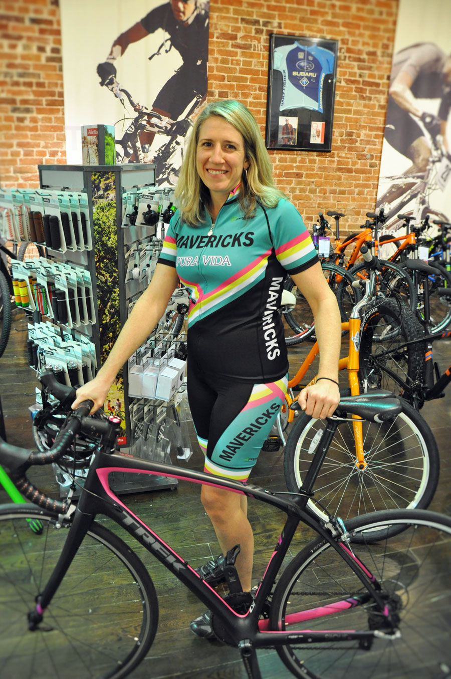 young woman dressed in cycling gear, standing with bike in bike shop