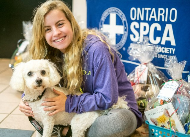 young woman bent down with a puppy at the SPCA