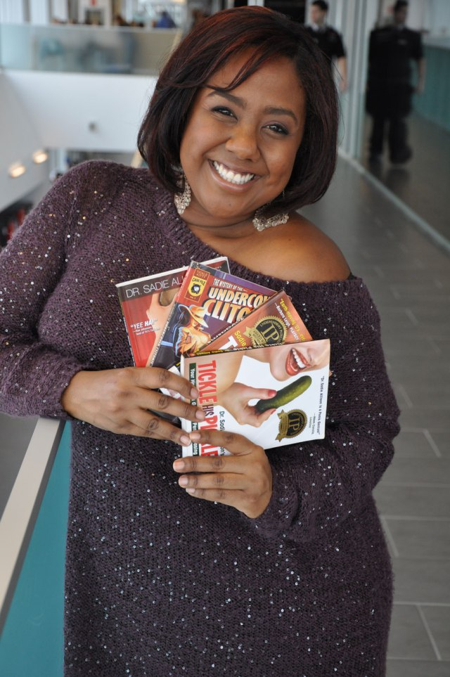 Woman holding up three sex improvement books; big smile