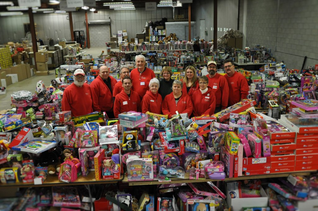 group photo of people in red sweatshirts among a pile of toys in a warehouse