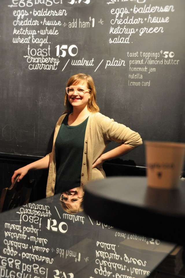 Woman with glasses stands in coffee shop with chalk board behind her