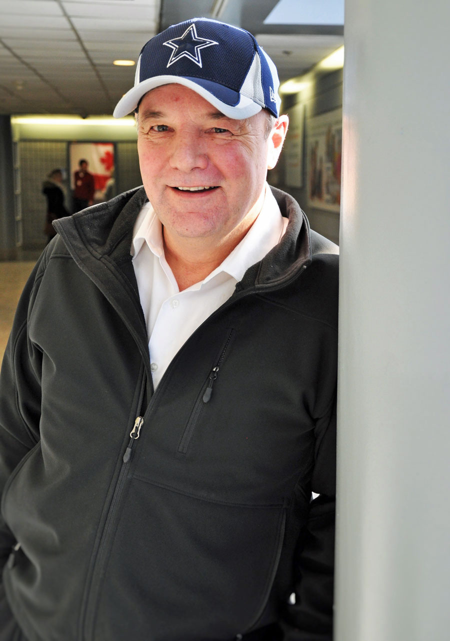 man in baseball hat, black jacket, white collar shirt leans against a poll in a hallway