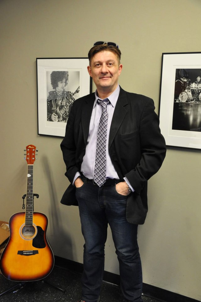 Man in suit jacket, tie and jeans stands with arms in pockets, guitar beside him, glasses on head