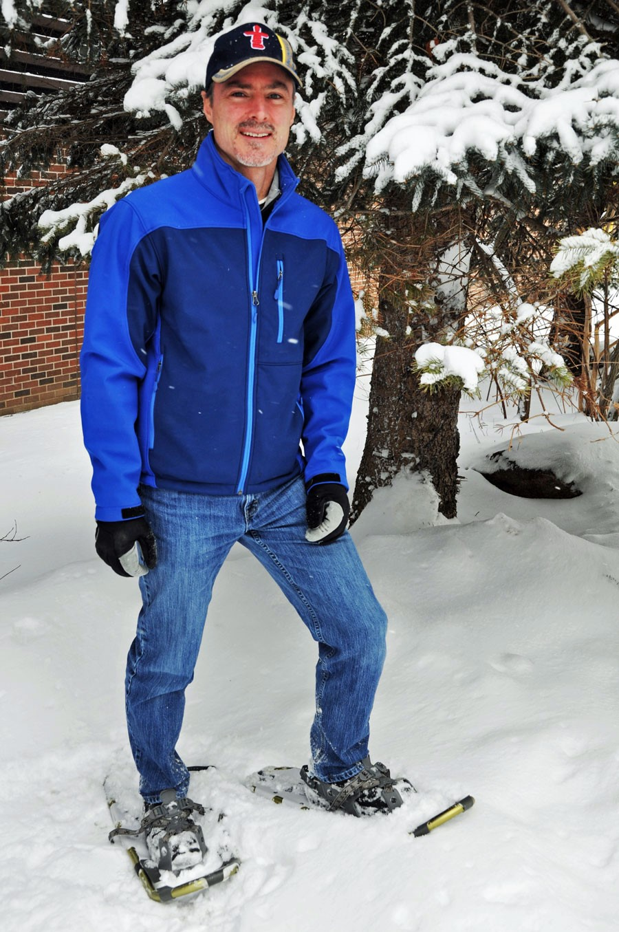 Man in blue ski jacket wearing snowshoes, standing just under a tree, baseball hat on