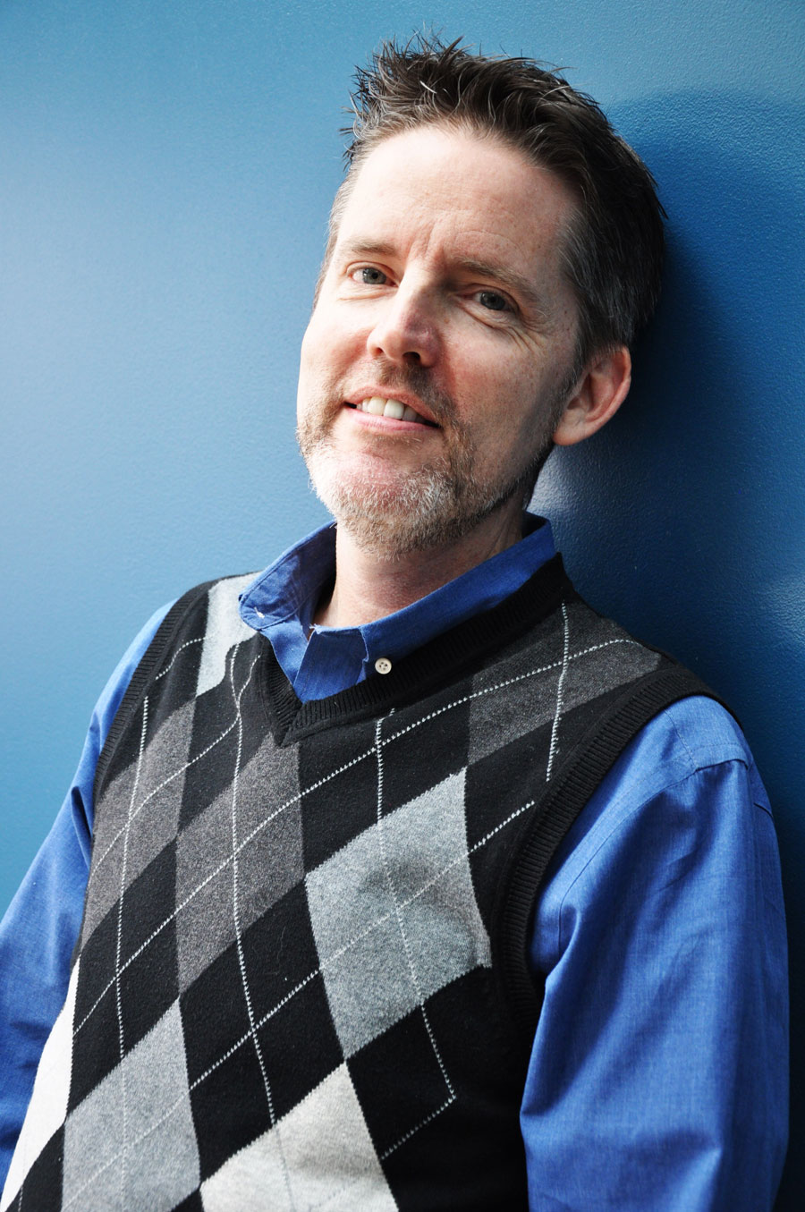 man leaning against blue wall, blue collar shirt on with sweater vest