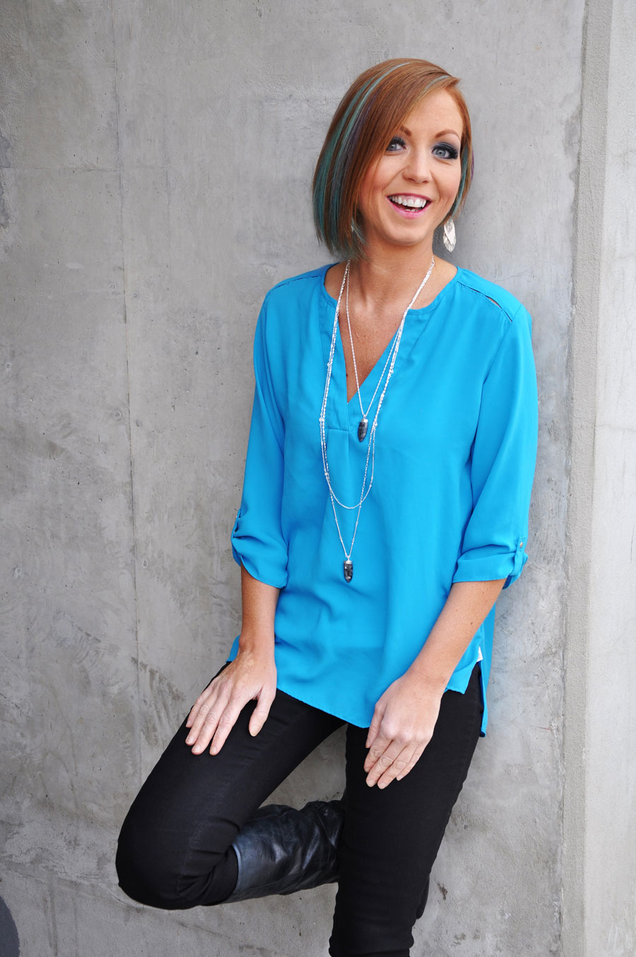 woman in a bright blue shirt and black pants leaning against a grey wall