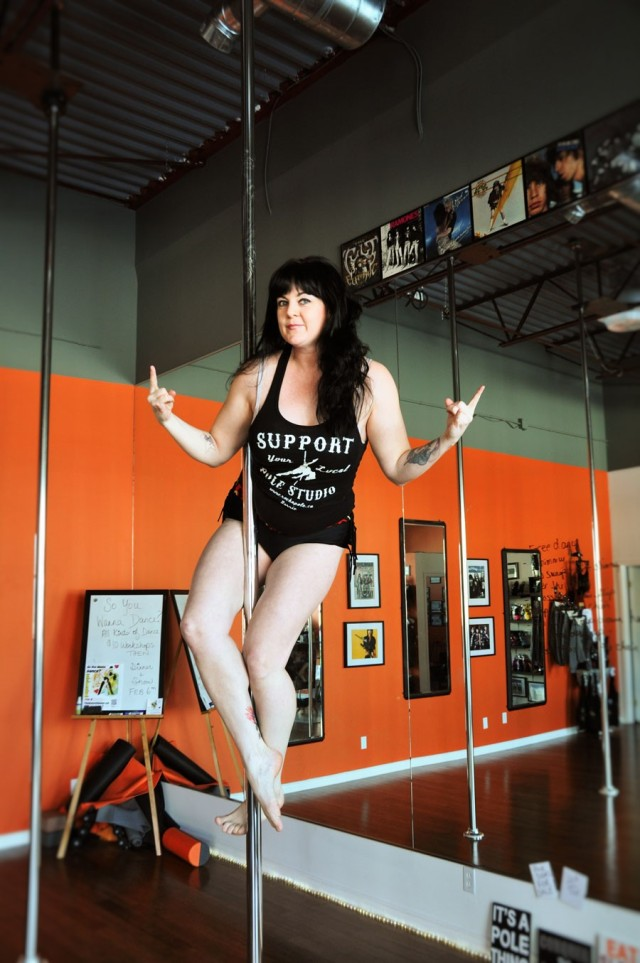 woman with long dark hair mid-air on an exercise pole, sitting