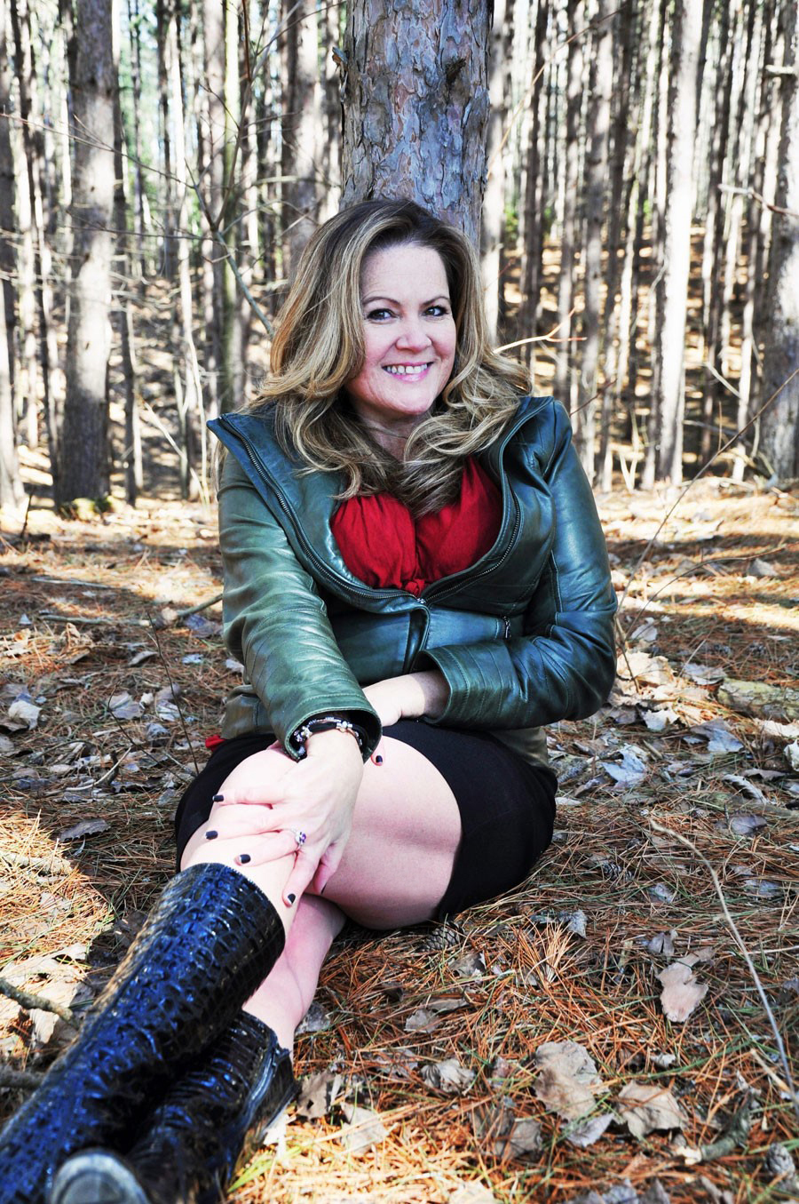 woman in red top, green leather jacket, black boots and skirt, sitting, leaning against tree in forest, all smiles