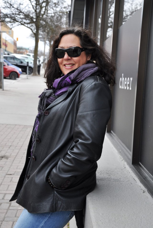 woman with dark hair, black sunglasses, black leather jacket, leaning against wall outside
