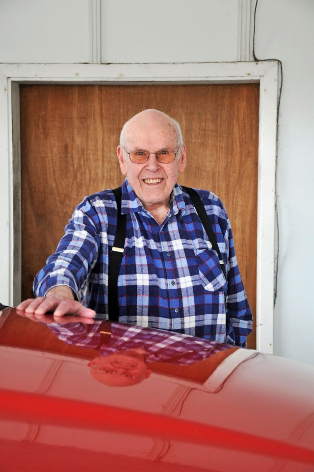 90-year-old man in plaid shirt standing behind the hood of his red truck