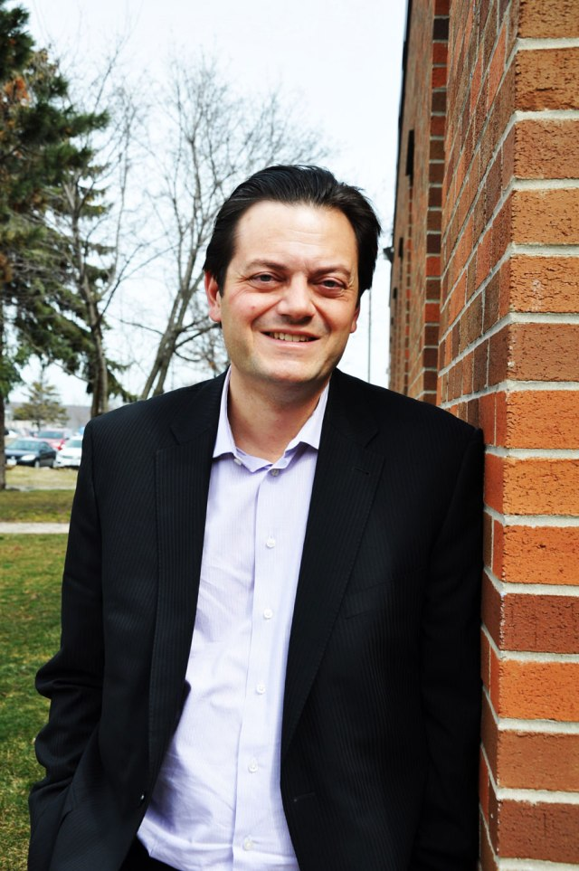 man in a black suit and white collar shirt leaning against red brick, smiling