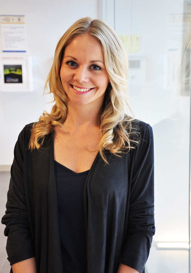 woman with long blonde hair standing in hallway; black top